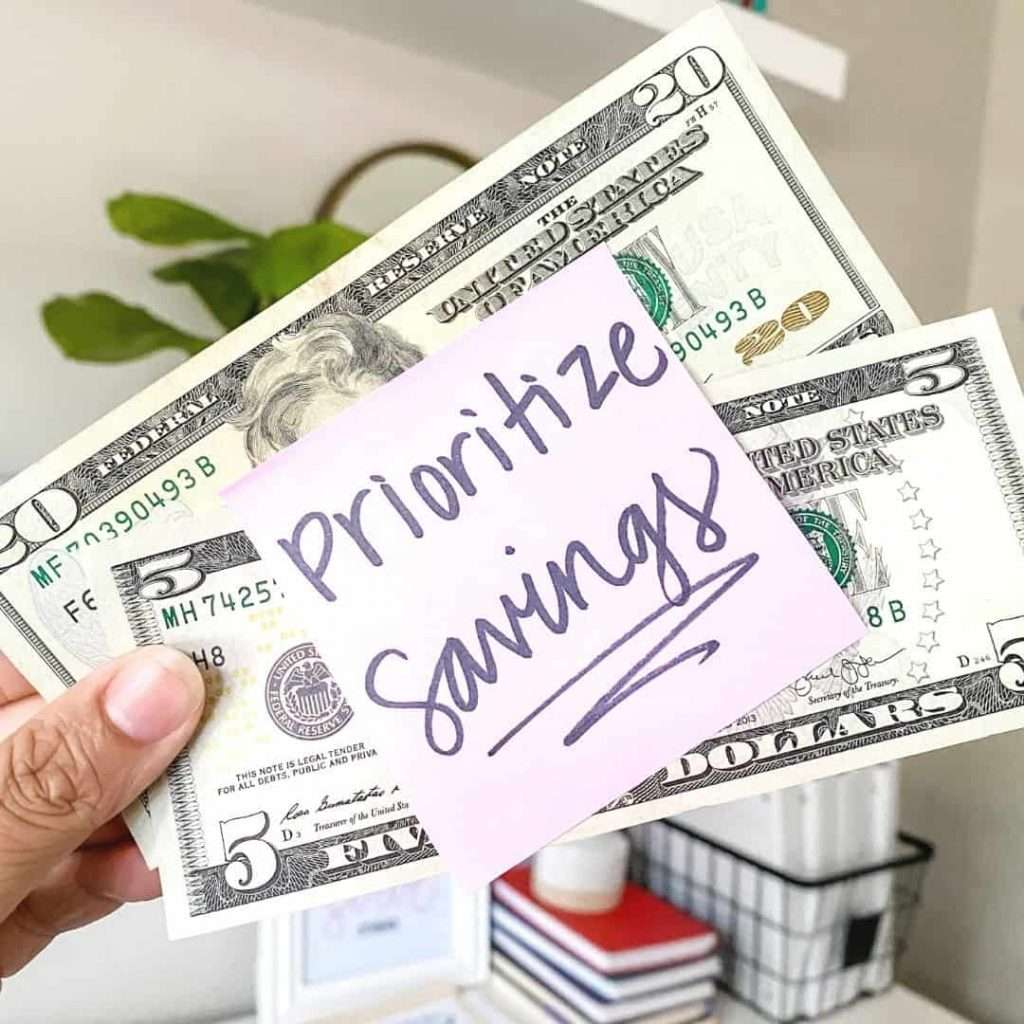 """money with note that says """"prioritize savings"""""""